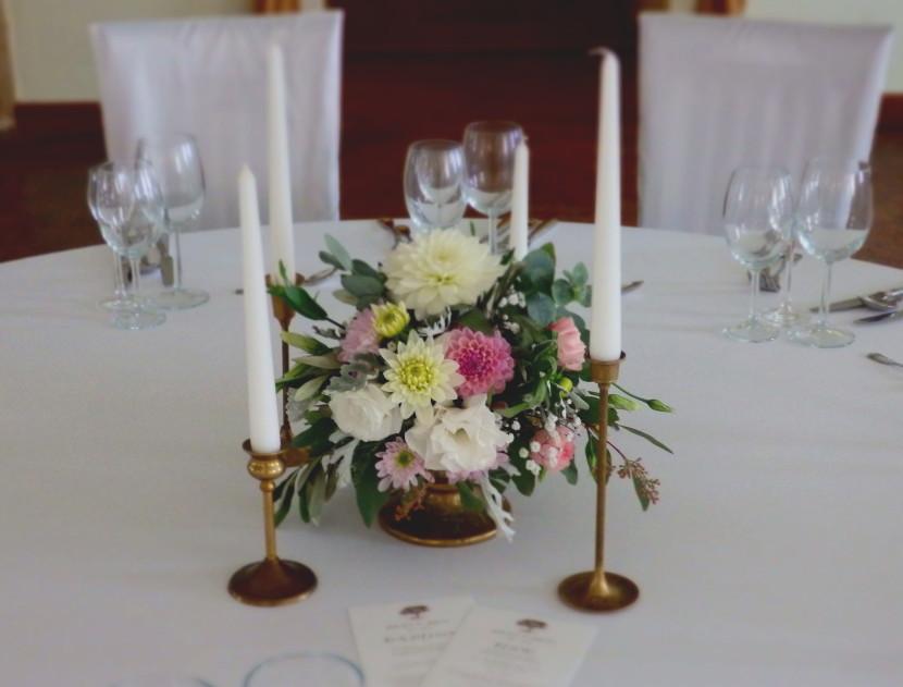 miedziane świeczniki i kompozycja kwiatowa